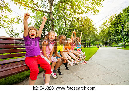 Stock Photo of Kids in row on bench with some mates excited.