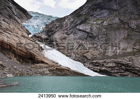 Stock Photography of A glacier on a rugged mountain at the water's.