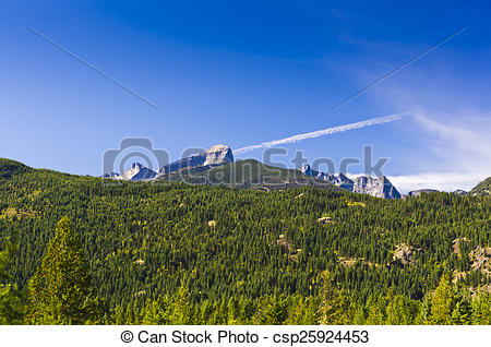 Stock Images of Rugged mountain peaks stand out against a blue sky.
