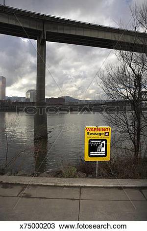 Stock Photo of Urban sewage runoff warning next to river x75000203.