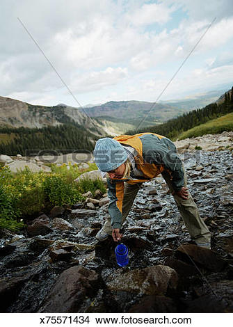 Stock Photo of Woman getting water from mountain runoff x75571434.