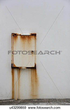 Stock Photograph of A wall mounted metal box with rust stains down.