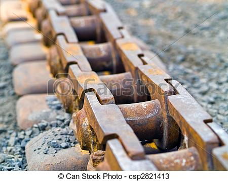 Stock Photos of Old Rusty Continuous Tracks on gravel ground.