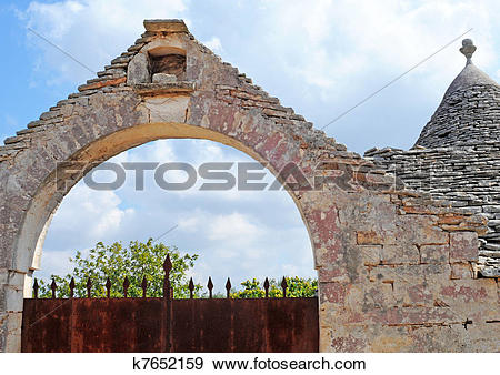 Stock Photograph of Farm with rusty gate and trulli house with.