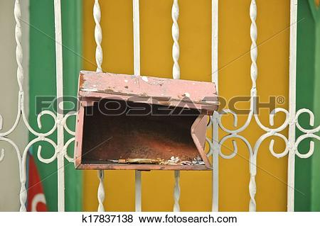 Pictures of rusty red broken letterbox hanged on a fence k17837138.