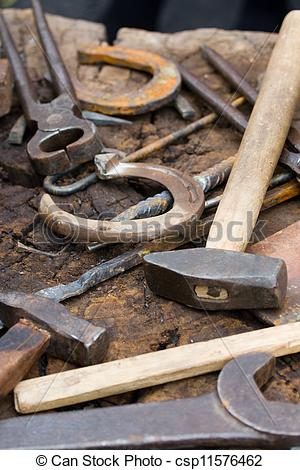 Stock Image of Rusty blacksmith tools and horseshoes on wooden log.
