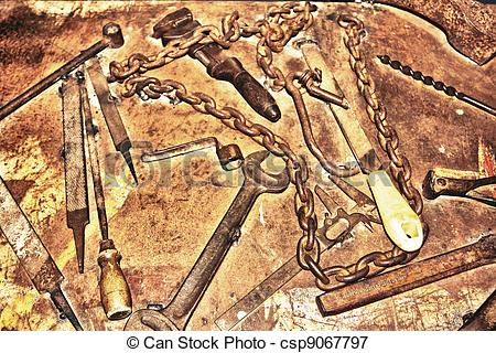 Picture of Antique rusty tools on an old wooden desk csp9067797.