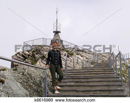 Stock Photograph of girl walks upstairs in mountains. Switzerland.