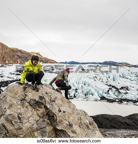 Stock Photo of Male and female tourist climbing on boulder at.