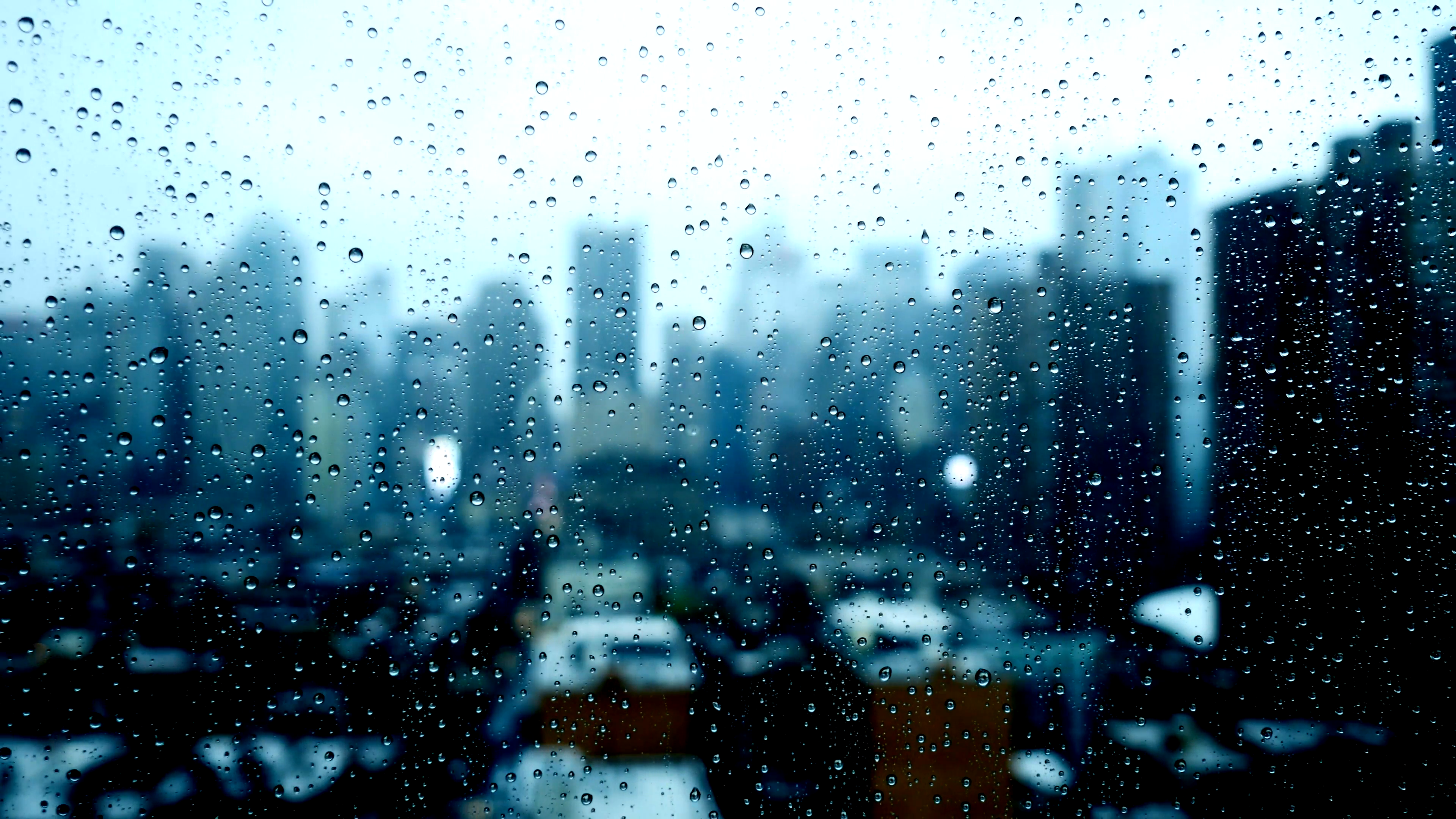 blurry city skyline window view. sad bad weather. rain drops background.