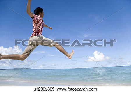 Stock Photograph of Man jumping on beach, Saipan, USA u12905889.