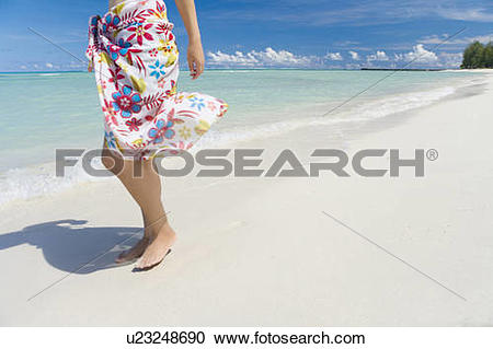 Stock Photography of Young woman standing on beach, copy space.