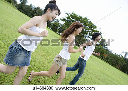 Stock Photography of Young people smiling and running on lawn.