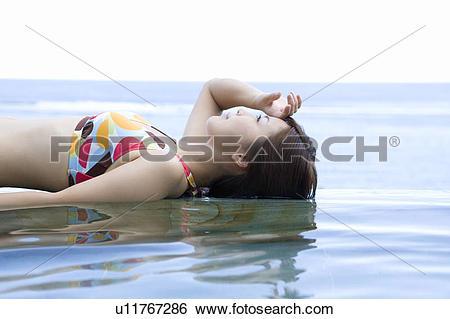 Stock Images of Young woman in a bikini lying on water, Saipan.