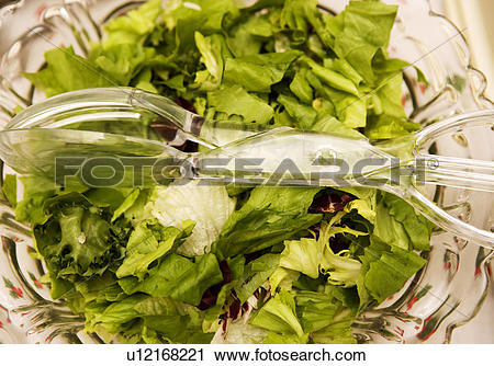 Stock Photography of Salad leaves and salad servers in a salad.