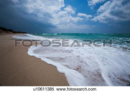 Stock Image of Empty, fine sandy beach with white foam of rough.