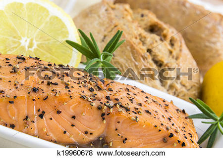 Pictures of spicy smoked salmon with lemon, rosmarin and bread bun.