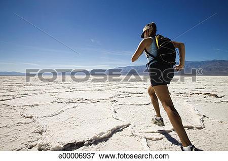Picture of Woman running in cracked desert landscape, Bonneville.
