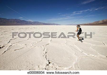 Stock Photo of Woman running in cracked desert landscape.
