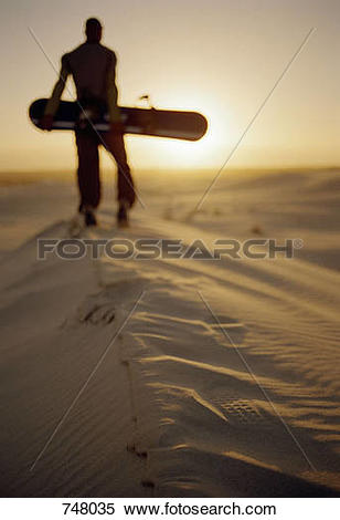 Stock Image of A man standing on a sand dune with a sand board.