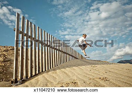 Stock Photography of Boy Jumping Fence on Sand Dune x11047210.