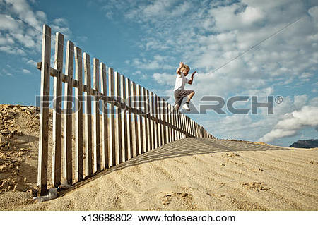 Stock Photo of Boy Jumping Fence on Sand Dune x13688802.