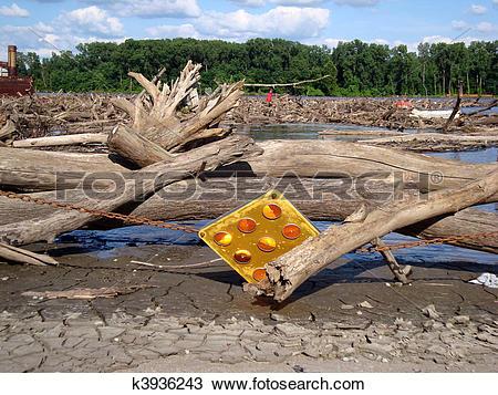 Stock Photo of Log jam behind barrier in Missouri river flood.