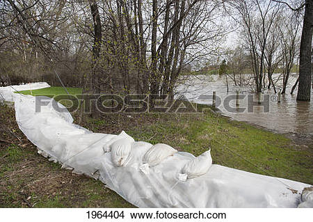 Stock Photo of sand bags line the river's shoreline to prevent.