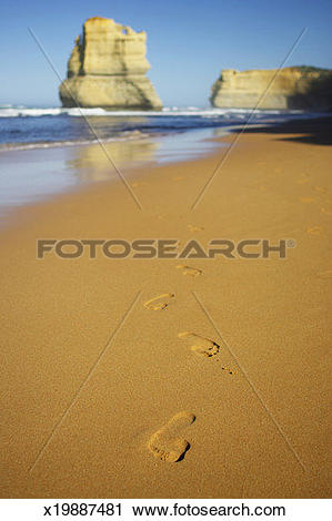Stock Photography of Footprints in sand on beach, rock formations.