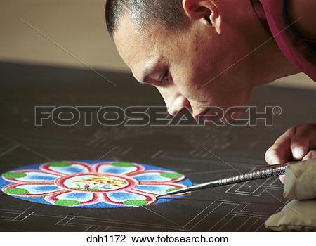 Stock Photo of A Tibetan Monk pours sand creating a Mandala sand.