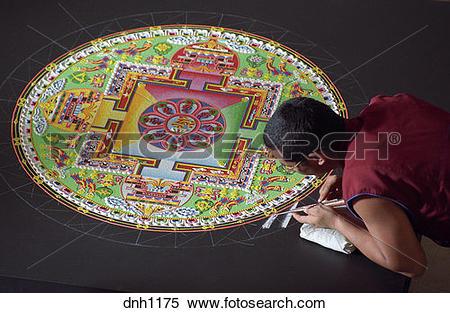 Stock Image of A Tibetan Monk pours sand creating a Mandala sand.