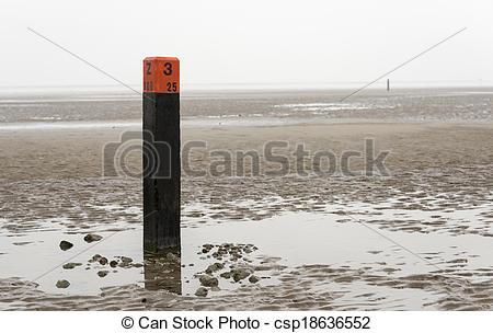 Stock Images of beach pole on wet sand and mud at low waterlevel.