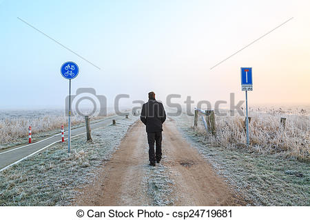 Pictures of Man walking on a sand road in a winter landscape in.