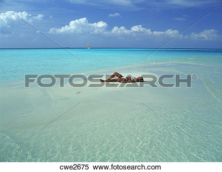 Stock Image of Woman alone on tiny sandbar in Indian Ocean with.
