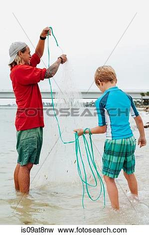 Picture of Teacher showing boy how to use cast net, Sanibel Island.