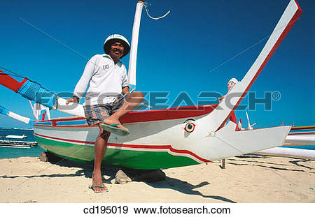 Stock Photograph of Outrigger boat helmsman. Sanur Beach. Bali.