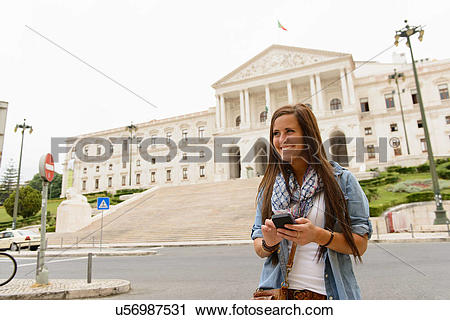 Stock Photography of Female tourist using smartphone outside.