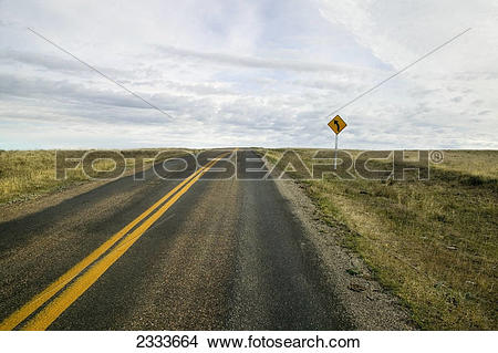 Stock Photo of An empty highway with a sign indicating a curve up.