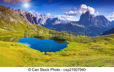 Stock Photo of Sassolungo mountain range at sunny summer day.