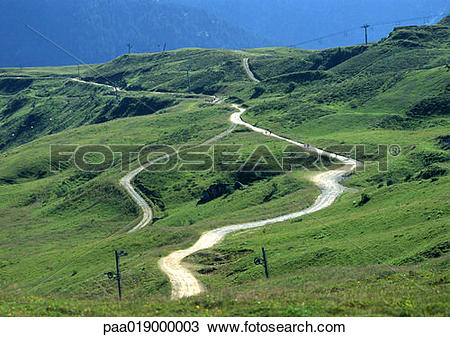 Stock Photo of France, Savoie, road winding through hilly area.