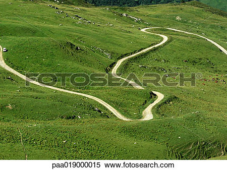 Stock Image of France, Savoie, winding road through grassy hills.