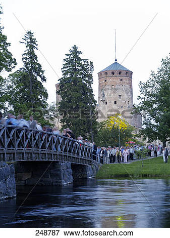 Picture of Tourists crossing bridge across river in front of.