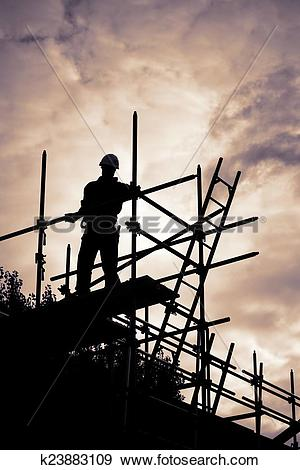 Stock Photograph of builder on scaffolding building site at sunset.