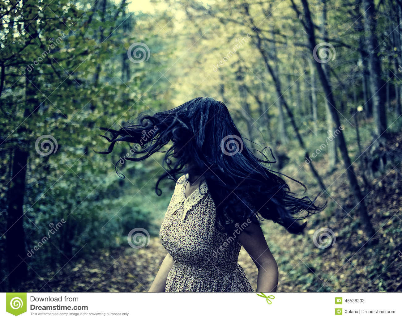 Scared Girl Running In The Forest Stock Photo.