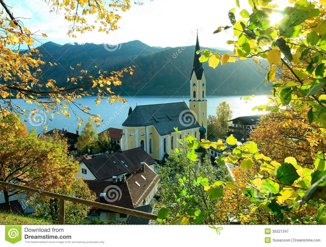 Autumnal View Through Branches To Schliersee Lake And Church.