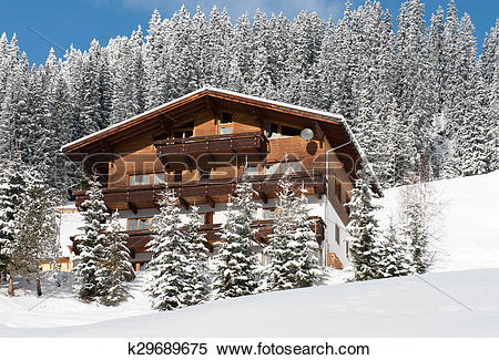 Stock Image of A chalet on the side of a mountain, near the.