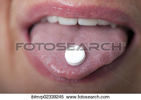 Stock Image of Homeopathic Schuessler salt tablet on a tongue.
