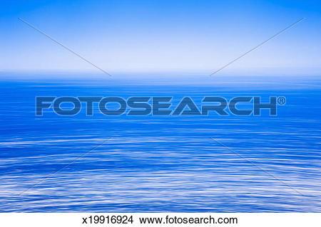 Stock Photo of Silky calm foggy open sea, blue sky, blue sea.