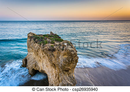 Stock Photo of Sea stack and waves in the Pacific Ocean at sunset.
