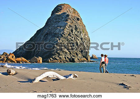Stock Photo of Women walking near sea stack rock formations at.